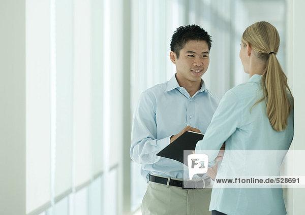 Zwei Büroangestellte im Flur im Gespräch