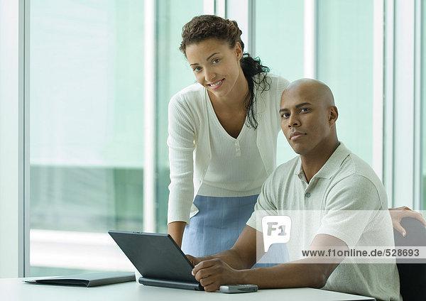 Geschäftsmann sitzt am Schreibtisch  während sich die Frau über die Schulter lehnt und lächelt in die Kamera.