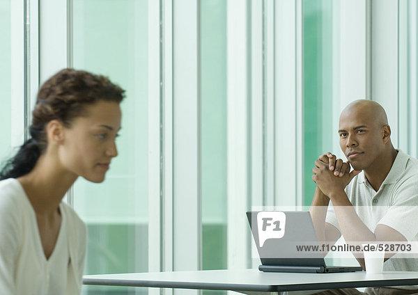 Mann sitzend mit Laptop  Blick auf weibliche Mitarbeiterin Mann sitzend mit Laptop, Blick auf weibliche Mitarbeiterin