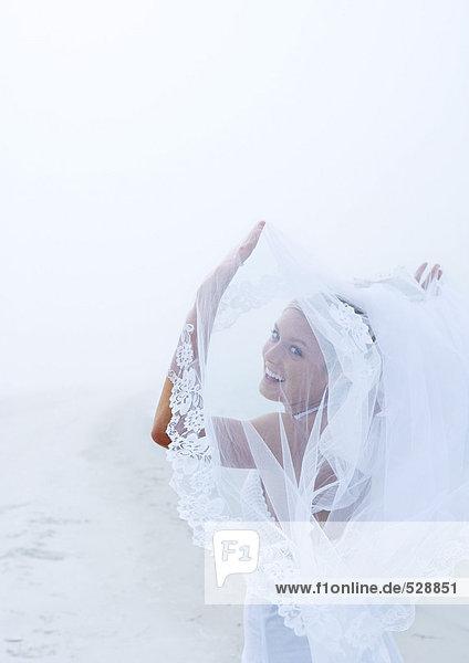 Braut hält den Schleier am Strand hoch