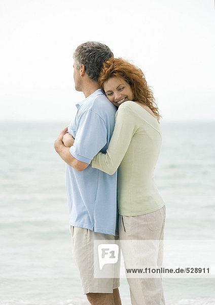 reifes Paar  Frau umarmt Mann von hinten