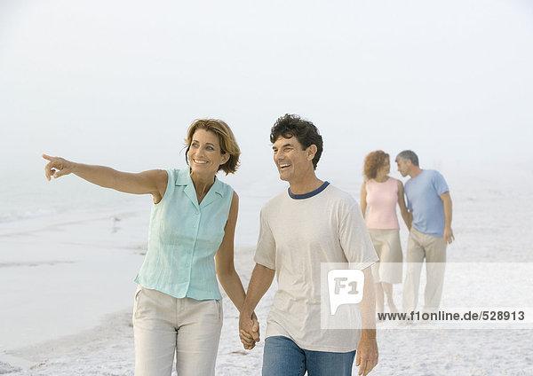 Ein reifes Paar  das am Strand spazieren geht  eine Frau  die in die Ferne zeigt.