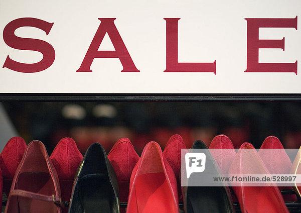 Verkaufsschild über Schuhregal