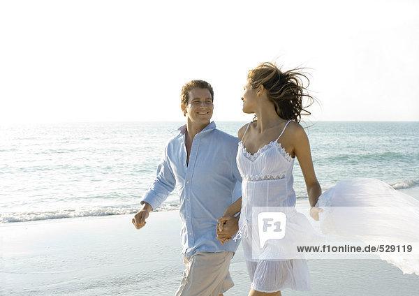 Ein Paar geht am Strand spazieren  lächelt sich an.