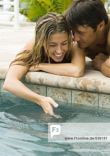 Junges Paar am Beckenrand liegend  Frau taucht mit der Hand ins Wasser