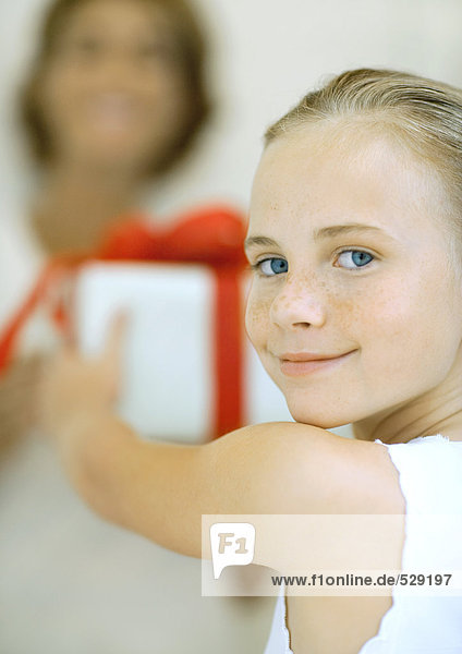 Girl holding out present to woman  smiling over shoulder at camera