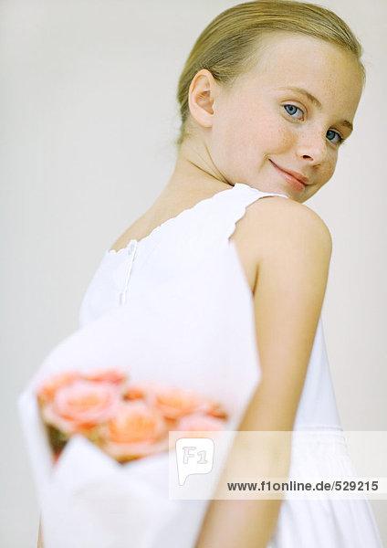 Mädchen mit Blumenstrauß hinter dem Rücken