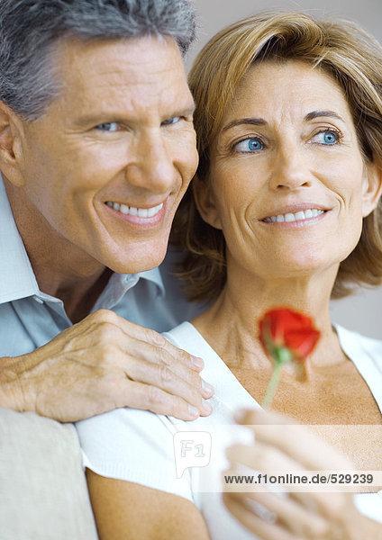 reifes Paar  Frau mit Rosenknospe