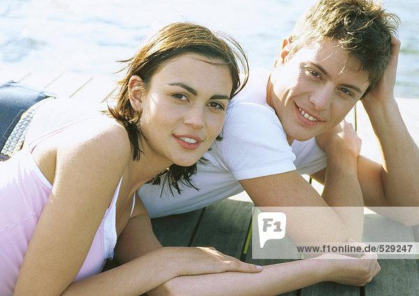 Young couple lying on dock