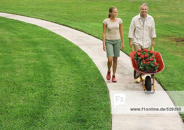 Vater und erwachsene Tochter gehen auf einem Gehweg und schieben eine Schubkarre voller Blumen.