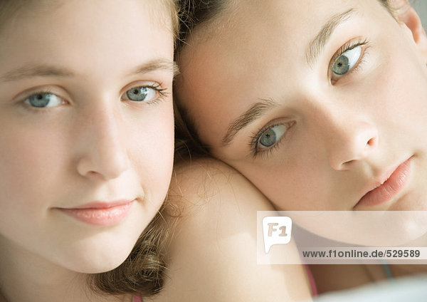Two preteen girls  one with head on other's shoulder