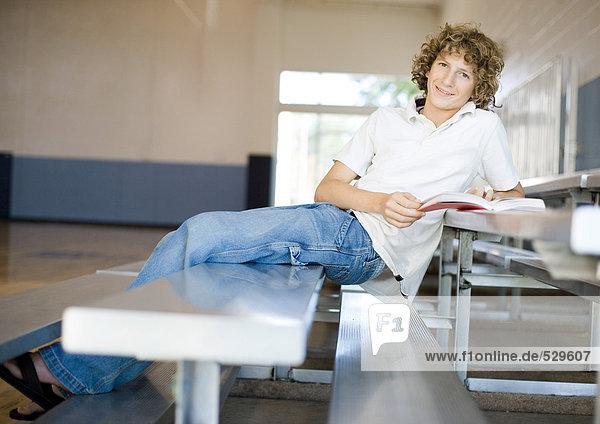 Teenager-Junge sitzt auf einer Tribüne in der Turnhalle  studiert