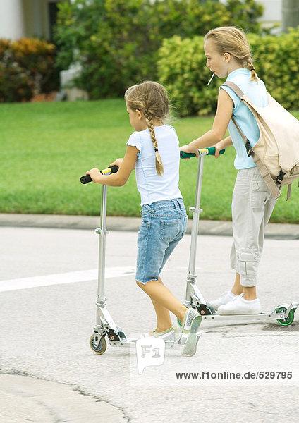 Vorstadtkinder fahren Roller auf der Straße