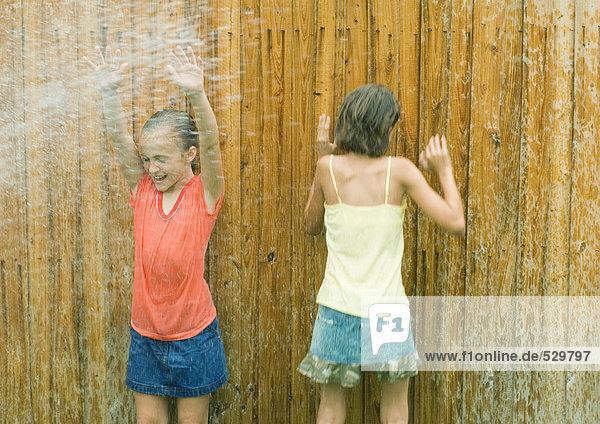 Mädchen  die im Spray stehen und nass werden