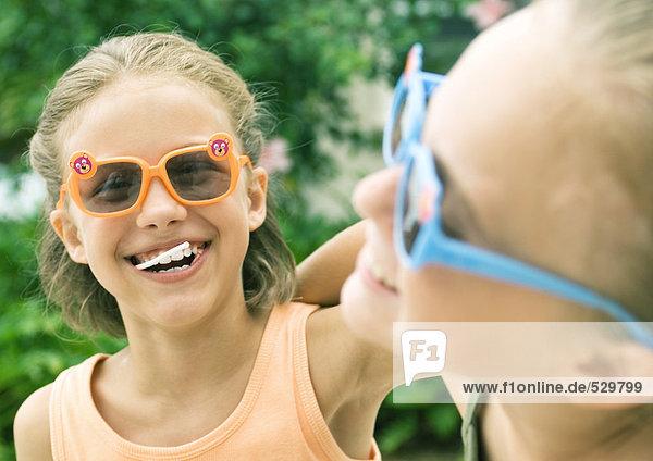 Zwei Mädchen mit Sonnenbrille und Lachen