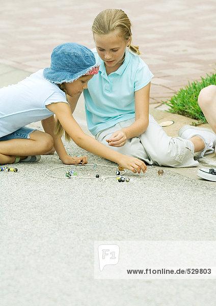 Vorstadtkinder beim Murmeln auf Asphalt