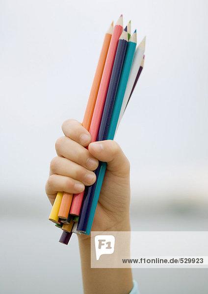 Kinderhand mit einer Handvoll Buntstifte