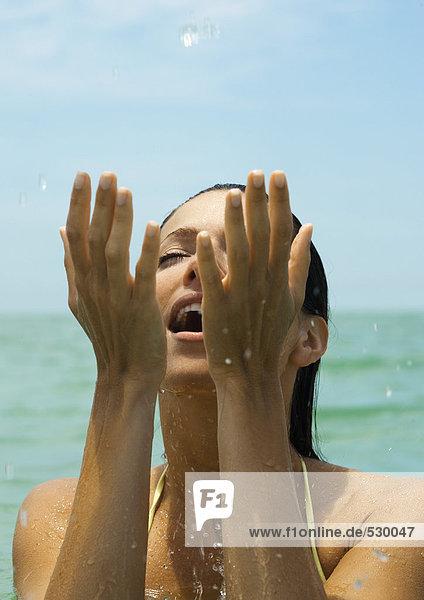 Frau im Wasser spritzend im Wasser  Augen geschlossen