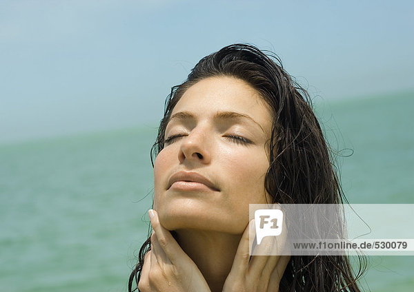 Frau hält Kopf  Augen schließen  Meer im Hintergrund