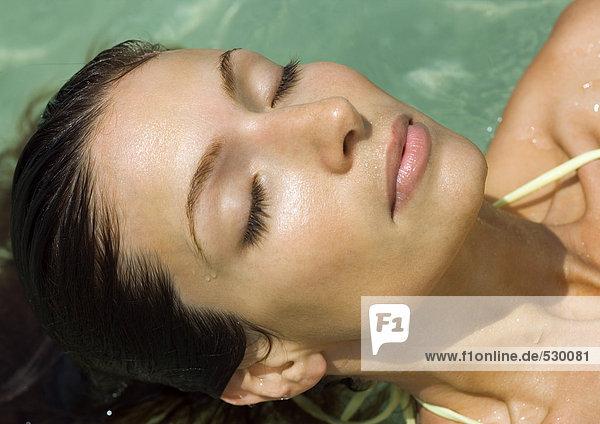 Frau im Wasser liegend mit geschlossenen Augen  Nahaufnahme des Kopfes