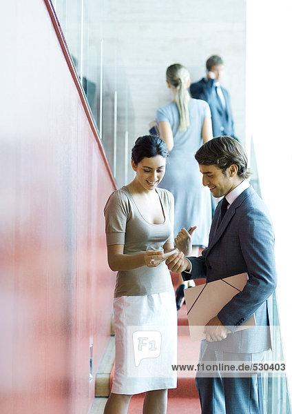 Führungskräfte beim Stehen  Sprechen und Austauschen von Visitenkarten
