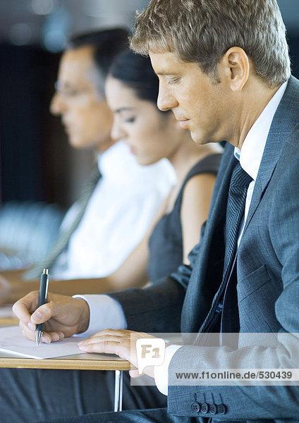 Führungskräfte  die im Seminar sitzen und sich Notizen machen