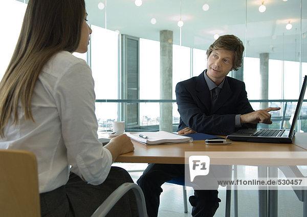 Geschäftsmann und Büroangestellte sitzen sich bei Tisch gegenüber und arbeiten