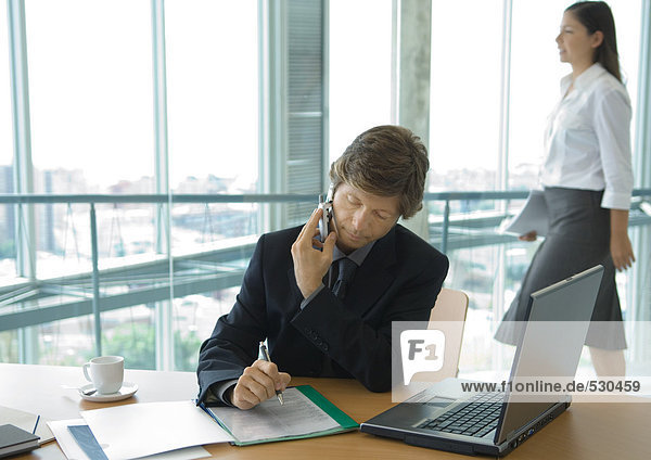 Geschäftsmann mit Handy am Schreibtisch  während Büroangestellte im Hintergrund vorbeigeht