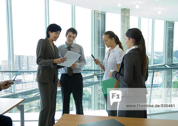 Four office workers standing  talking