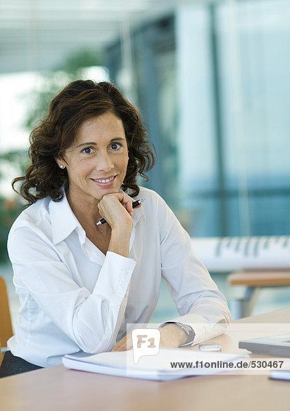 Geschäftsfrau am Schreibtisch sitzend  lächelnd vor der Kamera