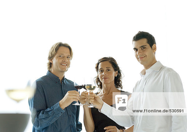 Three people clinking glasses of wine