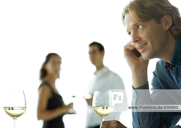 Man using cell phone  people drinking wine in background