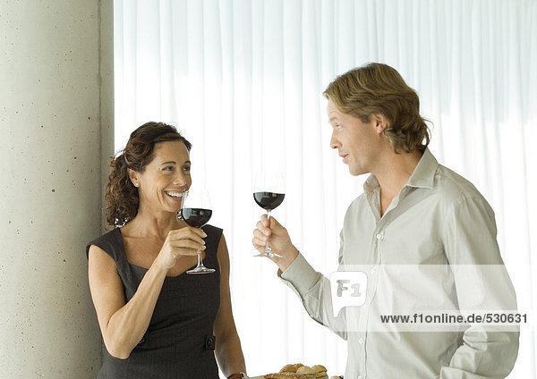Man and woman standing with glasses of red wine  chatting