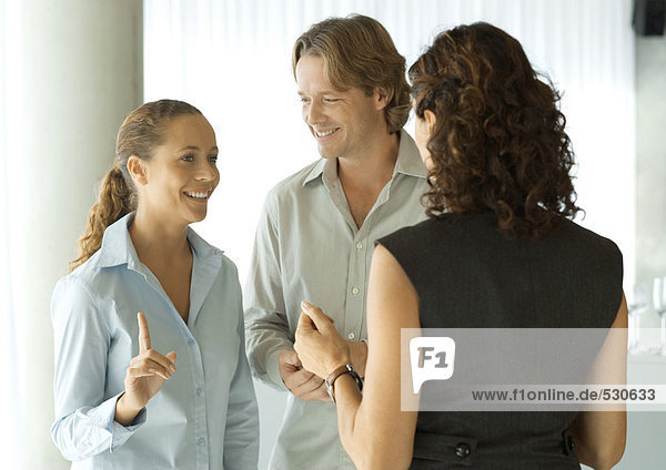 Three business people standing together talking  one woman raising finger