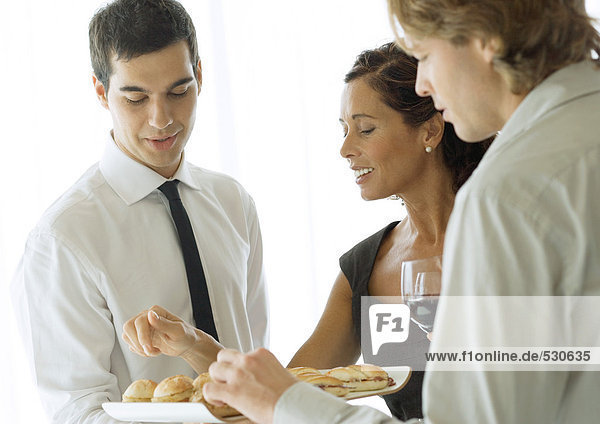 Server holding up tray of appetizers for man and woman during cocktail party