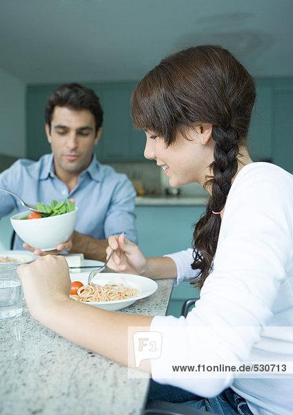 Vater und Tochter sitzen am Tisch und essen.