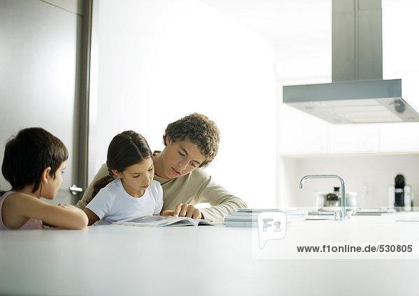 Jugendlicher Junge hilft der kleinen Schwester bei den Hausaufgaben