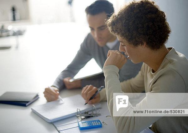 Vater hilft Teenager-Sohn bei den Hausaufgaben