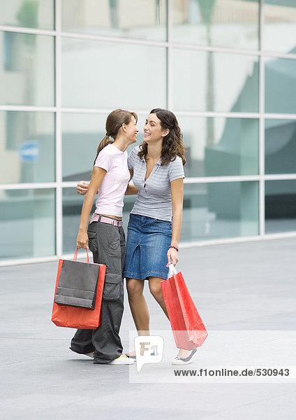 Teen girls holding shopping bags giving each other hug