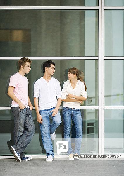 Teenager  die sich an die Wand lehnen und reden.