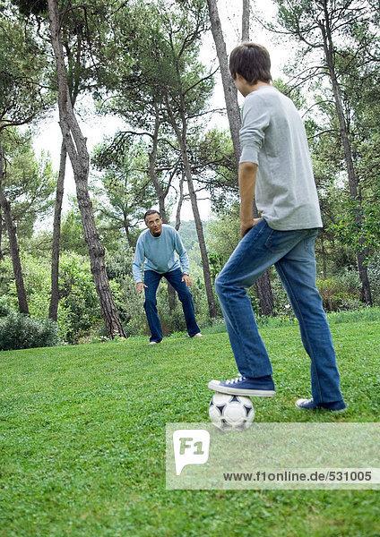 Erwachsener Mann und Teenager beim Fußballspielen