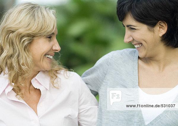 Reife Frau und erwachsene Tochter  die sich anlächeln.