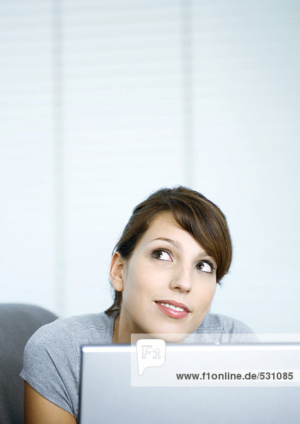 Frau  die vom Laptop aufschaut