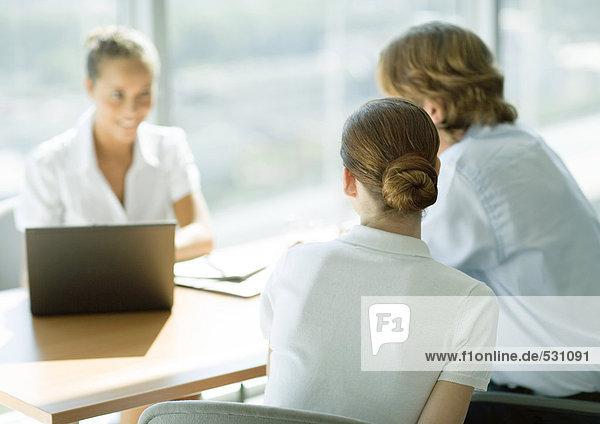 Man and woman sitting across table from smiling businesswoman  rear view