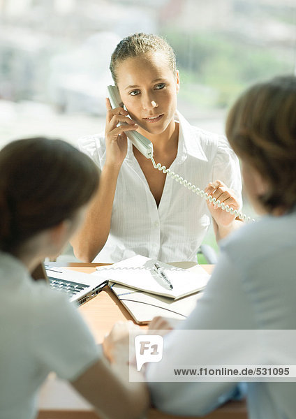 Professional woman using phone  sitting across table from couple