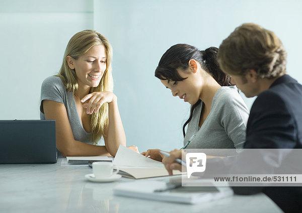 Drei Erwachsene sitzen am Tisch und schauen sich das Dokument an.