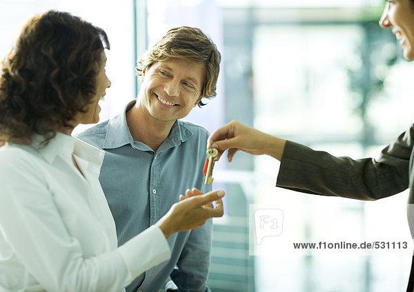 Paar lächelt sich an  als die Frau Schlüssel von der zweiten Frau annimmt