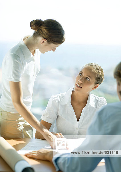 Woman pointing to blueprints and speaking to second woman