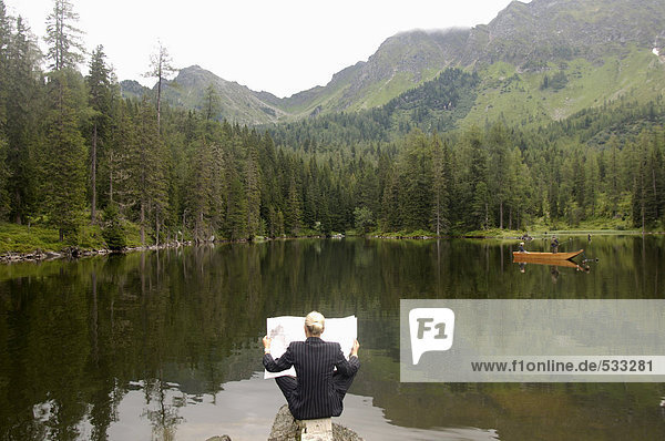 Businesswoman reading newspaper at lake  rear view