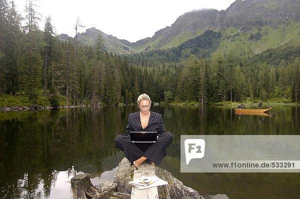 Geschäftsfrau am See sitzend mit Laptop